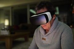 Occhiali di protezione d'uso di realtà virtuale dell'uomo senior a casa Fotografia Stock