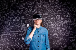 Occhiali di protezione d'uso di realtà virtuale della bella donna contro grande blac Immagini Stock