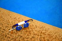 Occhiali di protezione di nuoto accanto allo stagno con acqua blu Fotografia Stock Libera da Diritti