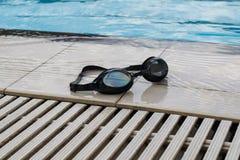 Occhiali di protezione di nuoto sull'orlo dello stagno Immagine Stock