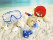 Occhiali di protezione e giocattoli dell'acqua nella sabbia Immagini Stock