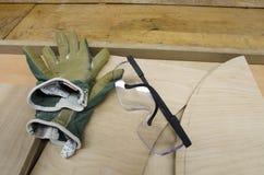 Occhiali di protezione e guanti del lavoro sul banco da lavoro di Woodend Fotografie Stock Libere da Diritti