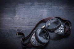 Occhiali di protezione sul bordo di legno d'annata Fotografia Stock Libera da Diritti