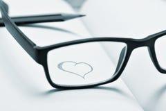 Occhiali e cuore assorbiti un taccuino, in bitonale Fotografie Stock