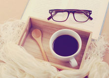 Occhiali e libro con caffè nero sul vassoio di legno Immagini Stock