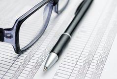 Occhiali e penna sopra le carte di rapporto Fotografie Stock Libere da Diritti