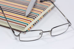 Occhiali e penna sul taccuino Fotografia Stock Libera da Diritti