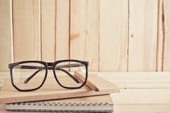 Occhiali, matita e taccuino sulla tavola di legno Fotografie Stock Libere da Diritti