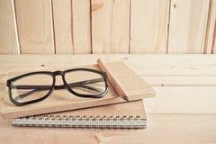 Occhiali, matita e taccuino sulla tavola di legno Fotografie Stock