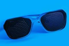 Occhiali medici con il foro negli ambiti di provenienza blu Fotografie Stock