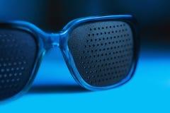 Occhiali medici con il foro negli ambiti di provenienza blu Fotografia Stock Libera da Diritti