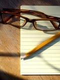 Occhiali, penna e blocco note Fotografie Stock Libere da Diritti