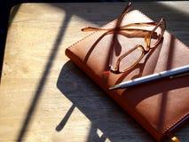 Occhiali, penna e taccuino Fotografia Stock