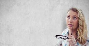 Occhiali premurosi della tenuta della donna contro la parete Fotografie Stock