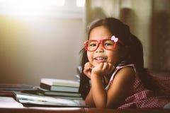 Occhiali sopra messi poco asiatici svegli che leggono un libro Immagine Stock