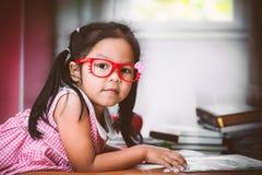 Occhiali sopra messi poco asiatici svegli che leggono un libro Immagine Stock Libera da Diritti