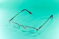 Occhiali su un backgro verde Fotografie Stock Libere da Diritti