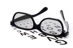 Occhiali su un diagramma dell'esame di occhio fotografia stock