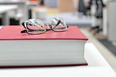 Occhiali sul libro Immagini Stock