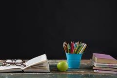 Occhiali sul libro aperto con il supporto e la mela della penna Fotografia Stock Libera da Diritti