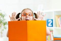 Occhiali weared ragazza divertente del bambino con il libro Fotografie Stock Libere da Diritti