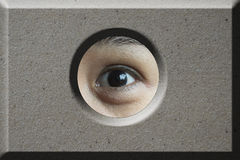 Occhio che guarda attraverso il foro in mattone Immagini Stock