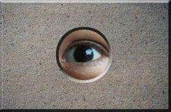 Occhio che guarda attraverso il foro in mattone Fotografia Stock