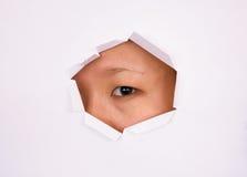 Occhio che osserva attraverso il foro Fotografie Stock