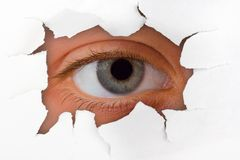 Occhio che osserva attraverso il foro su documento Fotografia Stock Libera da Diritti