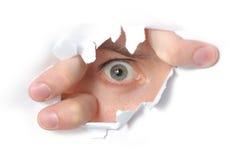 Occhio che osserva attraverso un foro in documento Fotografia Stock