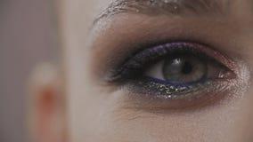 Occhio del lampeggiamento della donna del primo piano La bellezza compone dell'occhio verde al rallentatore video d archivio