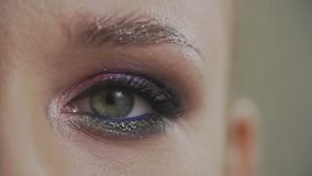 Occhio del lampeggiamento della macro donna del primo piano La bellezza compone dell'occhio verde al rallentatore stock footage