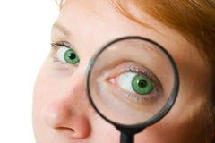 Occhio della donna che osserva tramite una lente d'ingrandimento. Immagini Stock