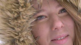 Occhio-ritratto del primo piano di bella giovane ragazza caucasica in cappuccio della pelliccia che si gira verso la macchina fot video d archivio