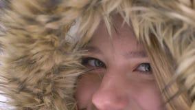 Occhio-ritratto del primo piano di bella giovane ragazza caucasica in cappuccio della pelliccia flirtingly che posa nella macchin video d archivio