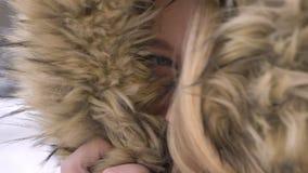 Occhio-ritratto del primo piano di bella giovane ragazza caucasica che si nasconde in cappuccio della pelliccia flirtingly che po video d archivio