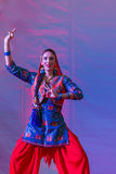 Occidental woman dances Indian style. An Occidental woman dances an Indian style dance  on a stage during Festival d'Oriente  (Festival of Orient). The event Royalty Free Stock Image