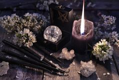 Black candles, crystal and sprig flowers on witch table. Occult, esoteric and divination still life. Halloween background with vintage objects stock image