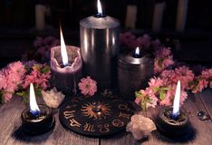 Black candles and zodiac circle with sakura flowers on witch table. Occult, esoteric and divination still life. Halloween background with vintage objects royalty free stock images