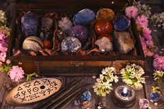 Box with magic crystals and stones, black candle and spring flowers
