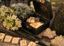 Close up with runes, crystals, white flowers and black candles. Occult, esoteric and divination still life. Halloween background with vintage objects stock photography