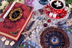 Witch book with magic spellings, black candles, flowers and cup of tea with zodiac circle. Occult, esoteric and divination still life. Halloween background with royalty free stock photos