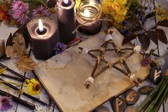 Black candles and pentagram on witch table. Occult, esoteric, divination and wicca concept. Alternative medicine and Halloween vintage background royalty free stock image