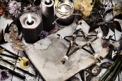 Open book with old empty pages, pentagram and black candles on witch table, toned image. Occult, esoteric, divination and wicca concept. Alternative medicine and stock photo