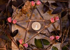 Wooden decorated pentagram with leaves, flowers and candle on paper, top view. Occult, esoteric, divination and wicca concept. Halloween vintage background royalty free stock photo