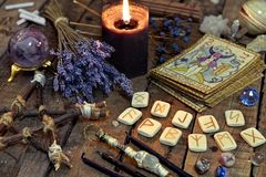 Tarot cards, ancient runes, black candle and pentagram. Occult, esoteric, divination and wicca concept. Mystic and vintage background with old objects Royalty Free Stock Photo