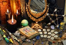 Tarot cards, magic wands, runes, black candles with mirror and old book. Occult, esoteric, divination and wicca concept. Mystic and vintage background with old Royalty Free Stock Image