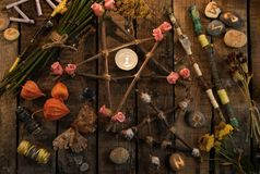 Pentagrams with magic wands, moth, runes and flowers on witch table, top view Royalty Free Stock Photography