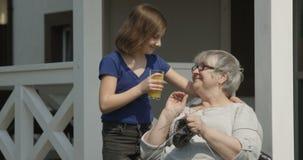 Occupandosi del nipote anziano sta portando il succo d'arancia alla nonna anziana che è tricottante e sorridente insieme all'aper stock footage
