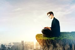 Occupation concept. Side view of young businessman sitting on cliff and using laptop. Sunlit city with copy space in the background. Occupation concept Royalty Free Stock Image